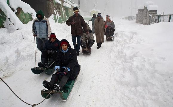 Tourists enjoy a sledge ride at Gulmarg