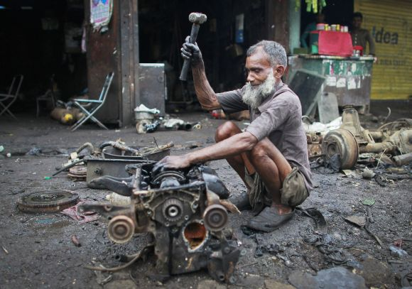 Hamid, uses a hammer to break an engine outside a scrapyard at an industrial area in Mumbai