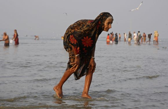 A devotee walks after taking a holy dip in Sangam, the confluence of the three holy rivers Ganga, Yamuna and Saraswati.