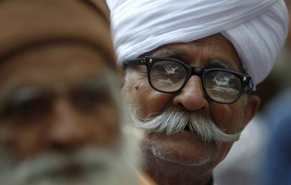 Supporters of veteran Indian social activist Anna Hazare listen to his speech during Hazare's day-long hunger strike in New Delhi.
