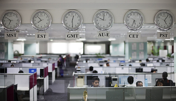 Workers pictured beneath clocks displaying time zones at an outsourcing centre in Bengaluru