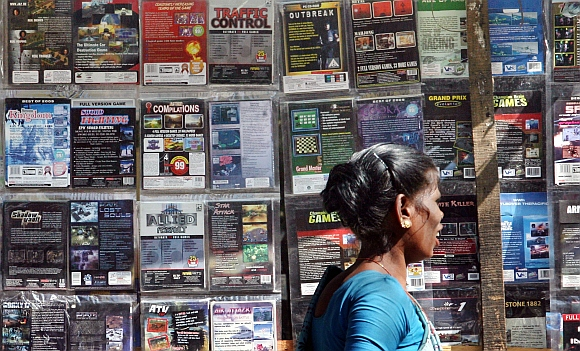 A woman walks past pirated DVDs and software on sale at a street side hawker shop in Mumbai