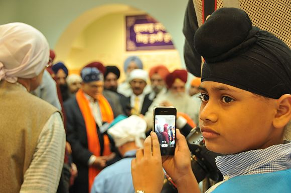 Jasbir, the son of Sita Singh, a priest killed in the attack, shoots photos of Krishna during his speech