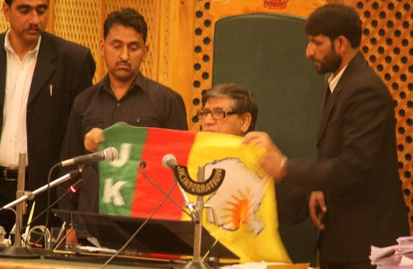 J&K assembly speaker Lone inspects the flag recovered from the youth