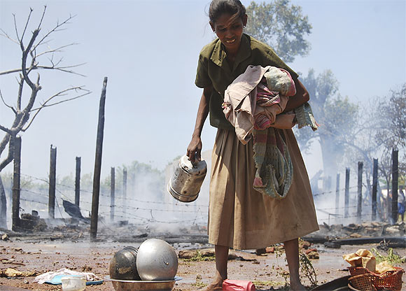 A Tamil refugee collects her belongings after a fire broke out in a camp in Vavuniya, northern Sri Lanka