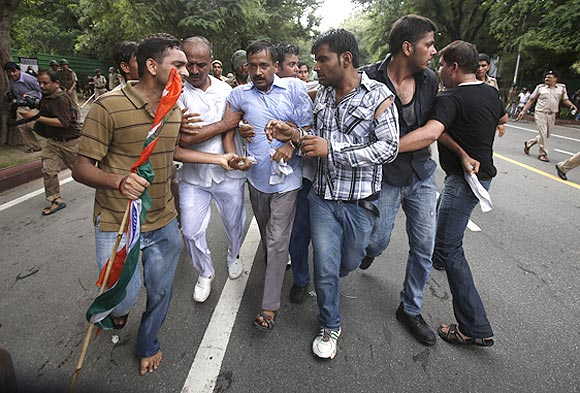 Arvind Kejriwal is shielded from the police by his supporters during a protest against corruption