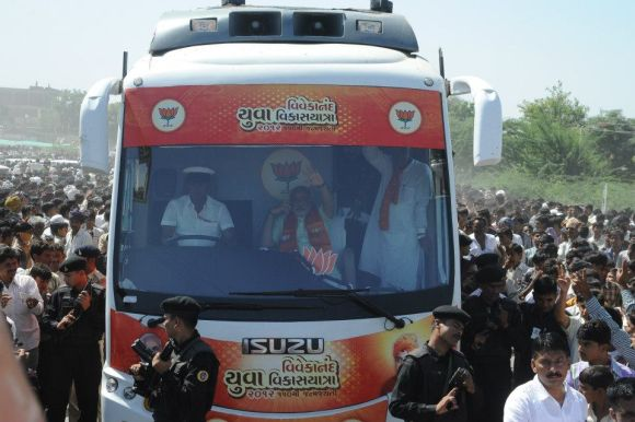 Modi waves to his supporters from his campaign bus during his ongoing yatra