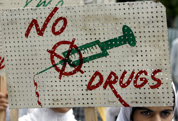 A schoolgirl holds a placard during a protest against the use of drugs