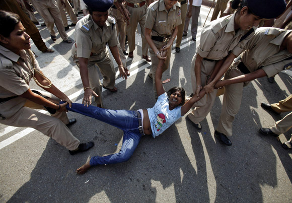 An activist of IAC, part of the anti-corruption social activist group led by Arvind Kejriwal, is being detained by police during a protest march in New Delhi