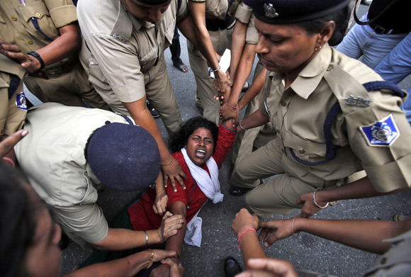 An IAC activist is being detained by police during a protest march in New Delhi