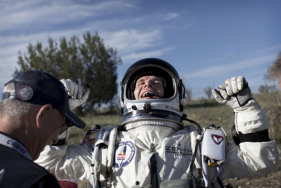 Baumgartner of Austria celebrates after he lands at the desert