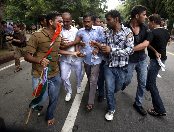 Arvind Kejriwal is shielded from the police by his supporters during a protest near Pri