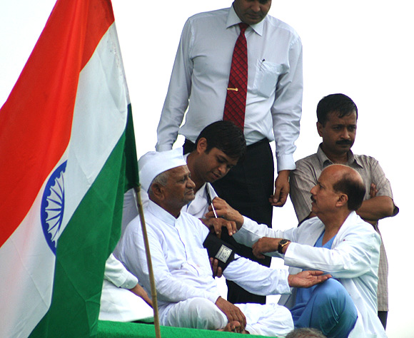 Doctors examine Anna Hazare at the Ramlila ground, New Delhi; Right: Arvind Kejriwal