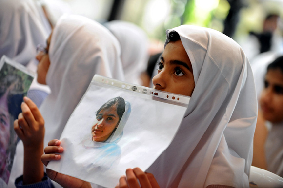 Students hold pictures of schoolgirl Malala Yousufzai, who was shot by the Taliban, during a tribute at the Pakistani Embassy in Abu Dhabi