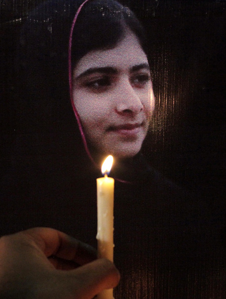 A man holds a candle next a picture of Malala Yousufzai, who was shot by the Taliban for speaking out against the militants and promoting education for girls, at a school in Lahore