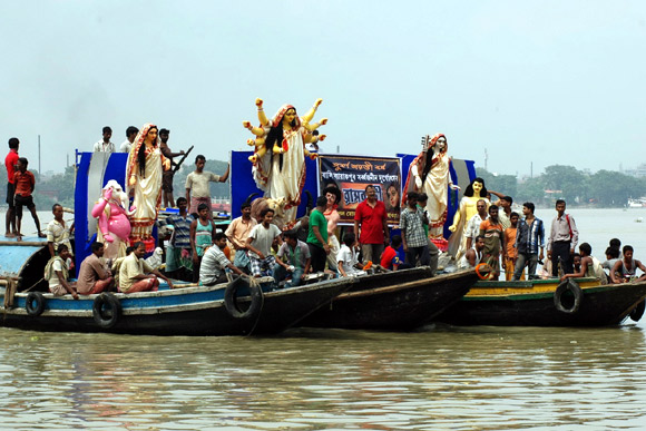 A Durga idol is ferried across the Ganga by members of Bali Sarbojonin Durgotsav Committee