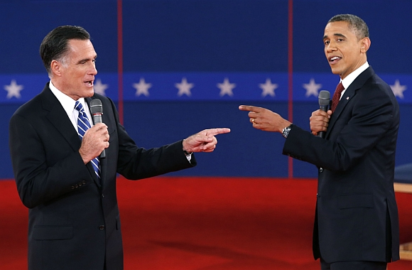 United States Republican presidential nominee Mitt Romney and US President Barack Obama gesture towards each other during the second US presidential debate in Hempstead