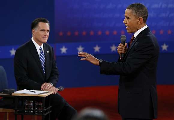 US President Barack Obama answers a questiion as  Romney listens during the second presidential debate in Hempstead, New York