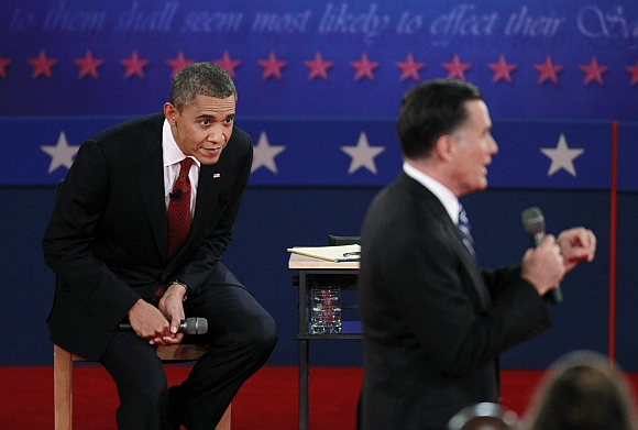 US President Barack Obama looks as Republican presidential nominee Mitt Romney speaks