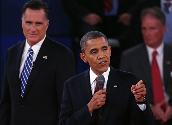 Republican presidential candidate Mitt Romney listens as US President Barack Obama answers a question during a town hall style debate at Hofstra University