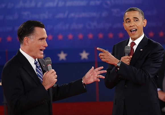 Republican presidential candidate Mitt Romney and US President Barack Obama talk over each other as they answer questions during a town hall style debate