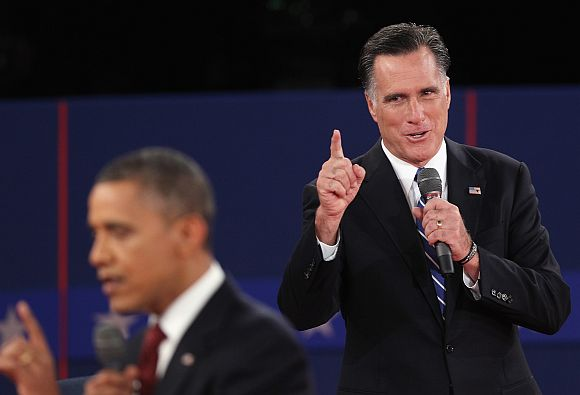 Republican presidential candidate Mitt Romney speaks as US President Barack Obama answers a question