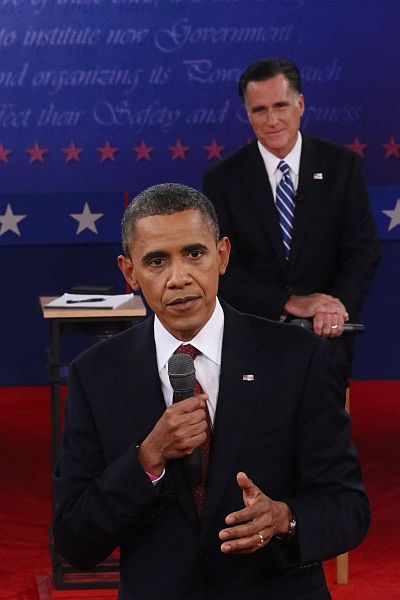 Republican presidential candidate Mitt Romney listens as US President Barack Obama answers a question