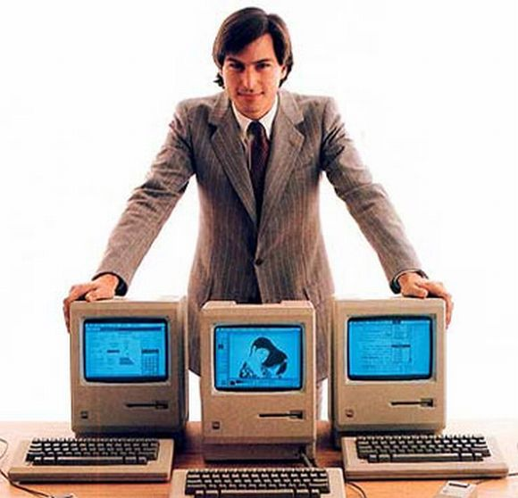 Steve Jobs poses with the 'beautiful device' called Macintosh