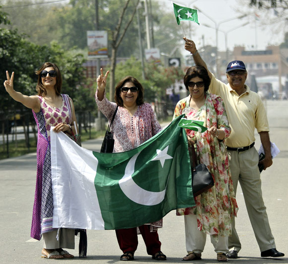 Pakistani visitors wave their national flags as they arrive in India through the check post at Wagah border.