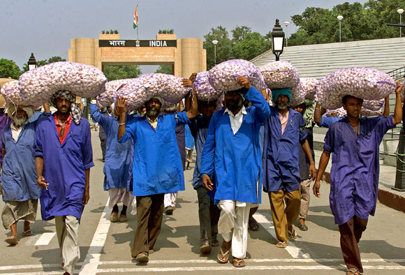 Indian porters carry garlic bags at the India-Pakistan joint check post at Wagah.