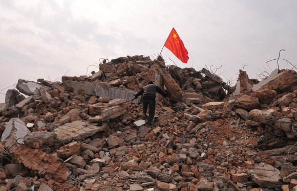 A local resident climbs towards a Chinese national flag planted at the top of his former house in Xi'an, Shaanxi province