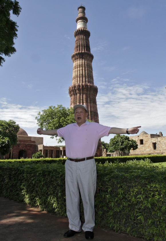 China's Defence Minister General Liang Guanglie poses in front of the Qutub Minar in Delhi