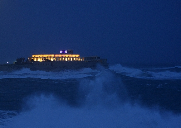 Waves crash on the rocks around the Dragonara Casino at dusk in St Julian's, Malta