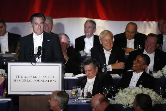 Obama listens to Romney speak at the Alfred E. Smith Memorial Foundation dinner in New York