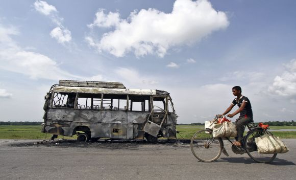 A bus that was burnt by a mob on the national highway near Rongia town during the Assam violence.