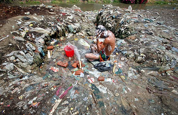 A man bathes from a broken water pipe line in a Noida slum in Uttar Pradesh