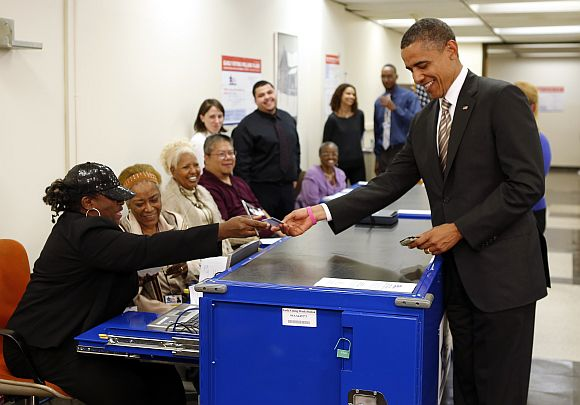 US President Barack Obama shows his drivers licence before casting his vote ballot early at the Martin Luther King Community Centre in Chicago