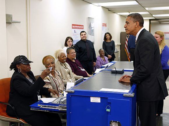 Polling workers double check the photo on US President Barack Obama's drivers licence
