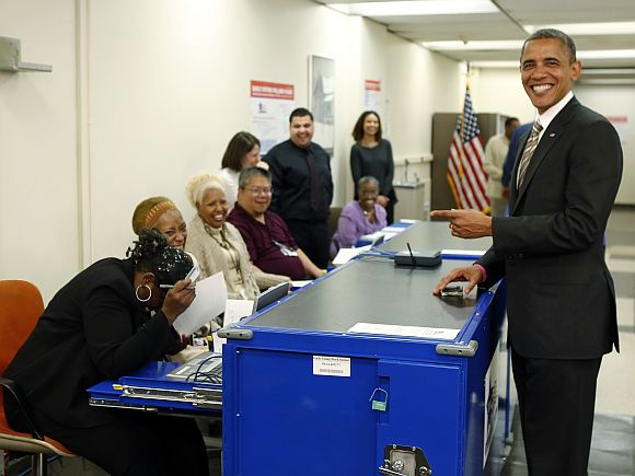 A polling worker laughs after US President Barack Obama mimicked the way she checked the photo on his driver's licence
