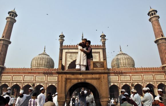 Muslim boys hug each other after performing Eid-ul-Azha prayers at the Jama Masjid in the old quarters of Delhi