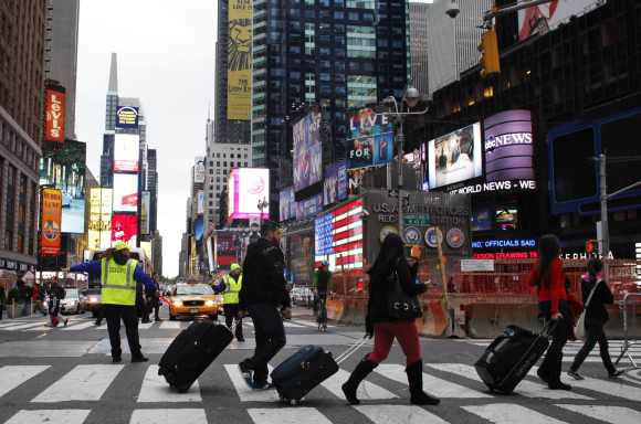 People pull their luggage at Times Square as Hurricane Sandy approaches New York