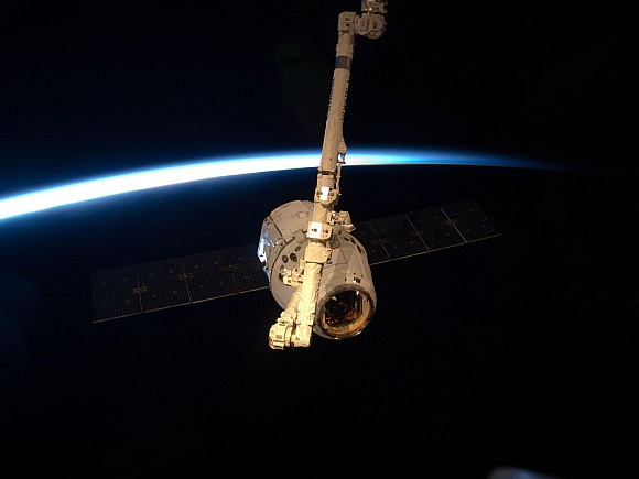With darkness, earth's horizon and thin line of atmosphere forming a backdrop, the SpaceX Dragon commercial cargo craft is grappled by the Canadarm2 robotic arm at the International Space Station