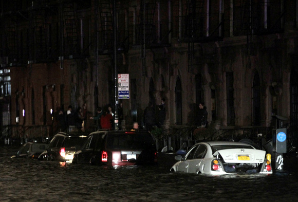 Flood waters brought on by Hurricane Sandy overrun cars in New York's lower east side