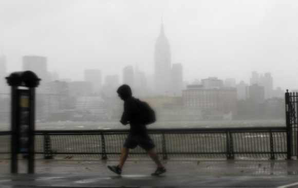 A man walks into the wind across the Hudson River from the skyline of New York in Hoboken