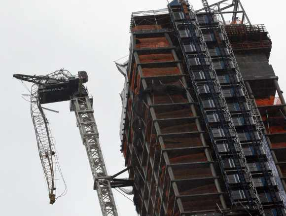 A partially collapsed crane hangs from a high-rise building in Manhattan