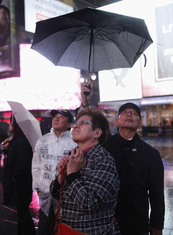 People keep under an umbrella in the mostly deserted Times Square ahead of Hurricane Sandy in New York