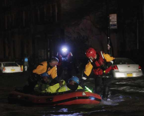 FDNY fire and rescue personnel lead a boat of ConEd power workers through flood waters after their power station was over fun by flood waters in New York