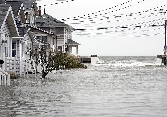 High tide begins to flood a street on the shoreline area of Milford, Connecticut as Hurricane Sandy approaches