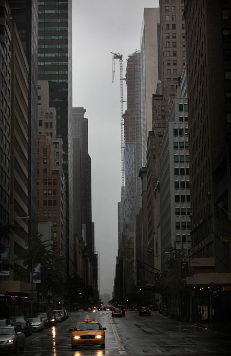 Part of a crane boom is seen hanging off a building under construction on West 57th Street in Manhattan, New York City