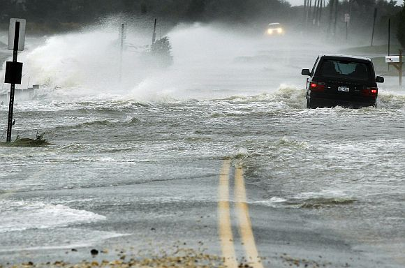 A car drives through water driven onto a roadway by Hurricane Sandy in Southampton, New York
